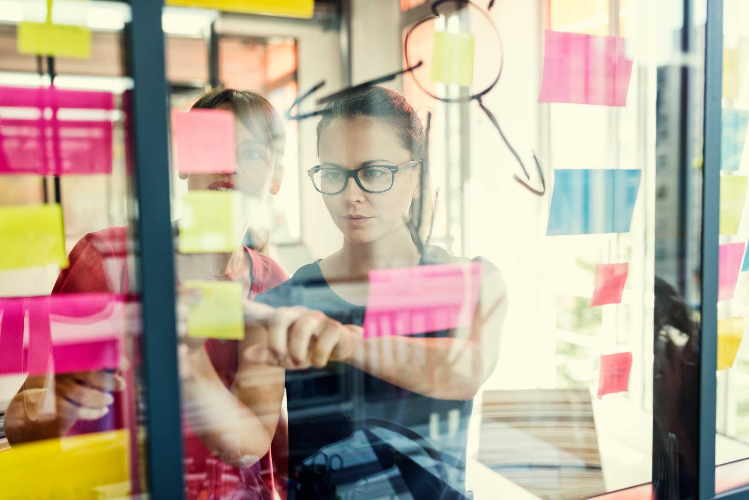Junge Frau klebt Post it´s auf eine Glasfläche im Rahmen eines Markenworkshops